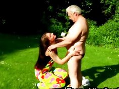 Gorgeous brunette teen blows her older lover's stiff rod in open air